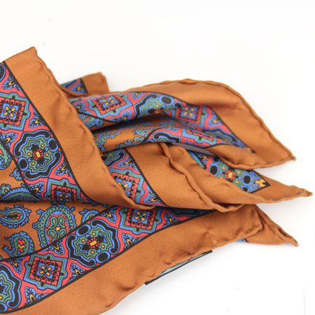 The burnt orange, as well as green and darker yellow in this Drakes pocket square are well suited to autumn and cooler months. Image courtesy exquisitetrimmings.com