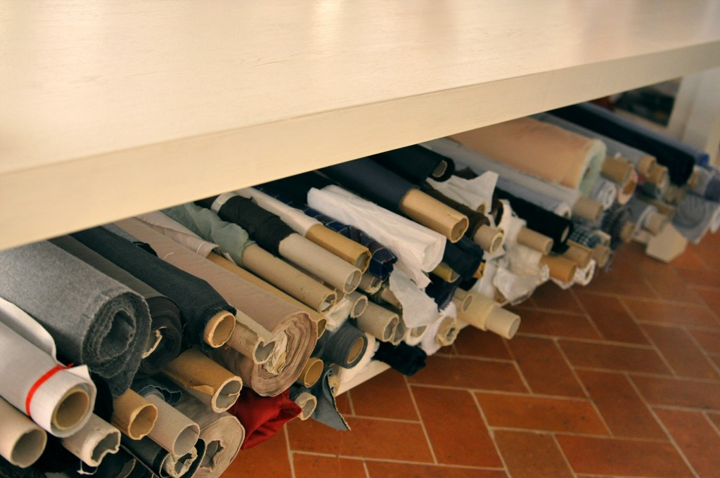 Bolts of cashmere fill the space under the cutting table