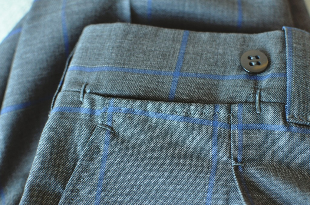 Bar-tacks surround the pleats and pockets, with pick stitching below the coin pocket and hand sewn belt loops. Note the matched checks on either side of the pleat which are hard to cut accurately.