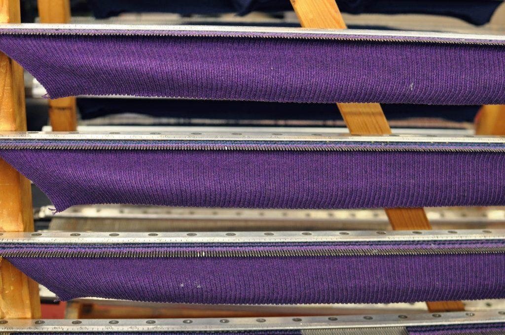 Purple thread, threaded onto needles and beginning to take shape